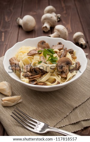 Dish of noodles with mushroom on wood table - stock photo
