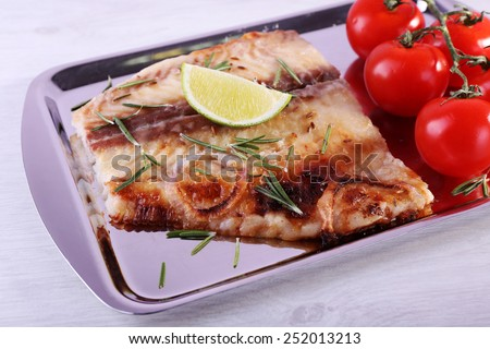 Dish of Pangasius fillet with rosemary and lime on metal tray and color wooden table background - stock photo