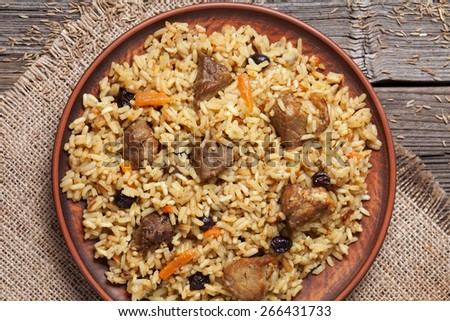 Dish of pilaf, national uzbek spicy meal with meat, rice, onion and garlic. Cooked with traditional recipe and served on vintage textile on wooden table background - stock photo