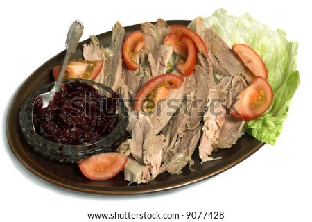 Dish of sliced turkey drumstick with cranberry sauce - stock photo