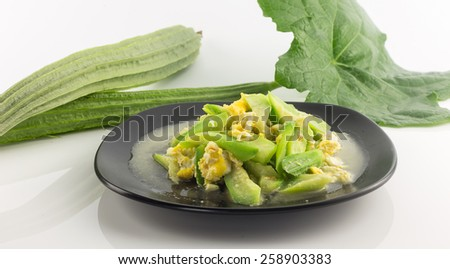 Dish of stir fried angled gourd with eggs  and fresh vegetable on white - stock photo