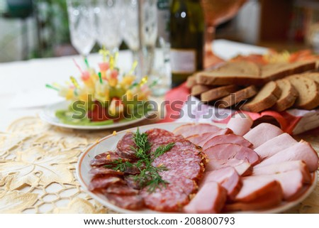 Dish with sliced meat products on the festive table - stock photo