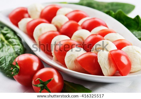 dish with sliced mozzarella cheese balls and ripe cherry tomatoes in caprese salad on the white table. horizontal format - stock photo