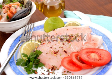 Dish with swordfish and contour mussel clam and tomato on table - stock photo