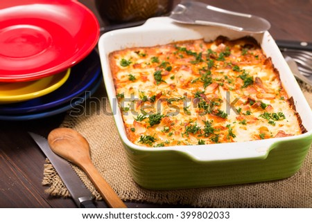 Dish with the baked potatoes on a kitchen table. The close up, toasted fried potatoes is cut by pieces and filled in with  sauce - stock photo