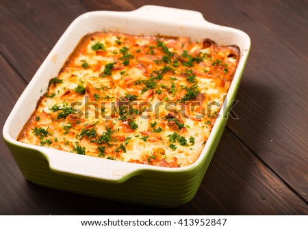 Dish with the baked potatoes on a kitchen table. The close up, toasted fried potatoes is cut by pieces and filled in with smetanny sauce - stock photo