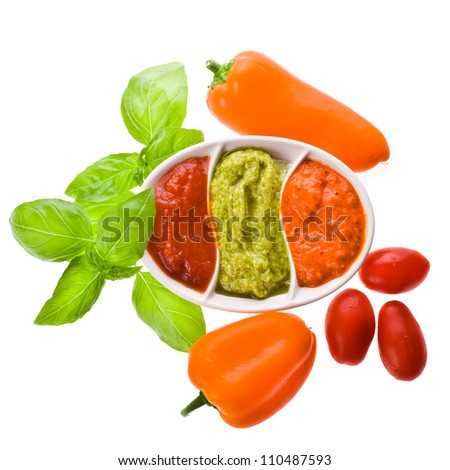 dishes for sauces with three different kinds of sauces, a branch of basil and paprica isolated on white background - stock photo