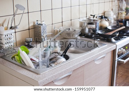 Dishes in the sink - mess in the kitchen - stock photo