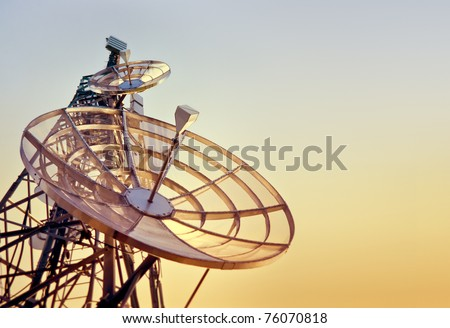 dishes on a telecommunications tower at the sunset - stock photo