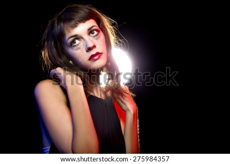 Disheveled drunk or female high on drugs at a nightclub.  She is alone like an outcast.  Lit with red and blue color gels for nightclub effect. She is alone like an outcast. - stock photo