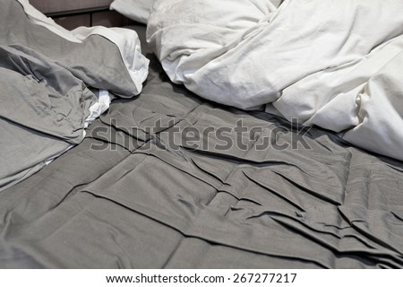 Disheveled sheets and pillows of an unmade bed - stock photo