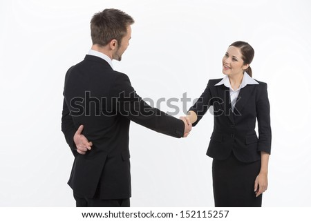 Dishonest business partner. Two business partners shaking hands while man holding his fingers crossed behind back - stock photo