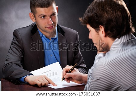 Dishonest businessman convincing his client to sign a contract - stock photo