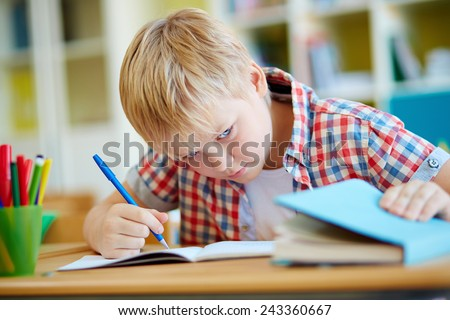 Dishonest schoolboy looking the right answer in book during test - stock photo