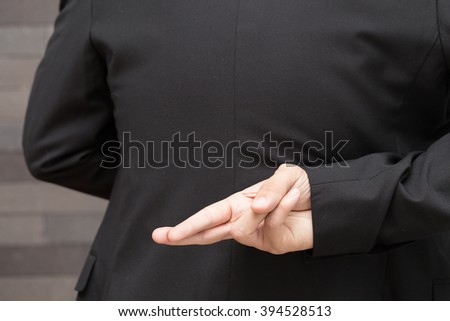 Dishonesty, Business fraud concept, Businessman showing fingers crossed - stock photo