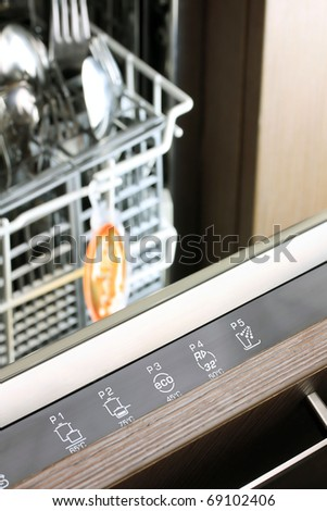 dishwasher control panel in front of fork and spoon basket - stock photo