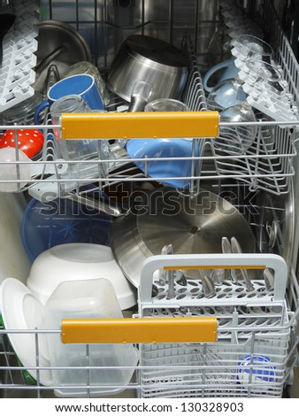 Dishwasher loaded with dirty dishware - stock photo