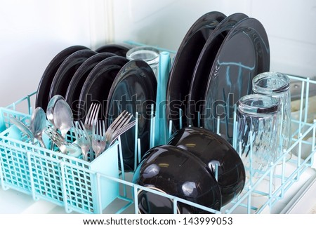 Dishwasher rack loaded with clean plates, glasses and silverware. - stock photo