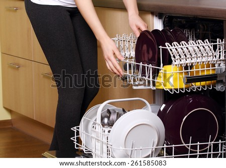 Dishwasher. Young woman in kitchen doing housework. Puling out dishes from dishwasher - stock photo