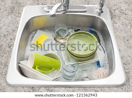 Dishwashing. Bright dishes soaking in the kitchen sink. - stock photo