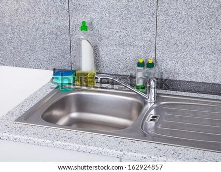 Dishwashing Liquid With Sponge On Silver Kitchen Sink - stock photo