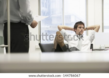 Disinterested businessman reclining on chair and ignoring boss in office - stock photo