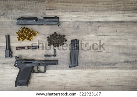 Dismantled gun pistol with new and used bullets on wooden background. - stock photo