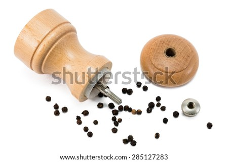 dismantled wooden pepper mill lying between peppercorns - stock photo