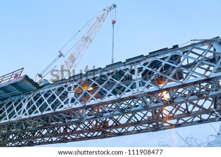 Dismantling of the old bridge. Work in the evening. - stock photo