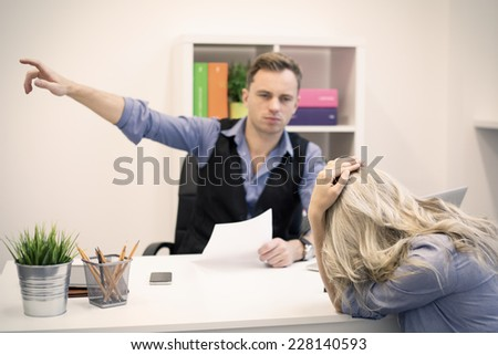 Dismissal, firing and sacking concept. Boss is showing doors to young unhappy female employee. - stock photo