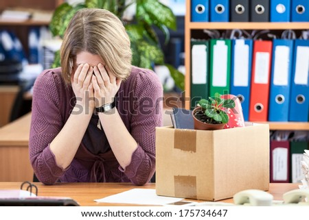 Dismissed woman crying, last time sitting at your desk - stock photo