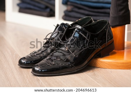 Display of a pair of black lacquered leather man shoes in a store or showroom - stock photo