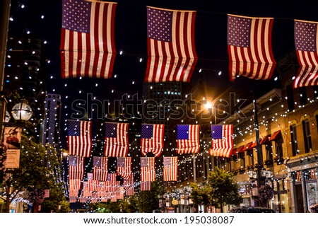 Display of American flags hanging above street with twinkling lights - stock photo