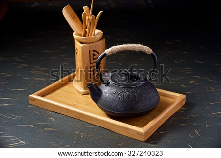 Display of ancient Chinese teapot on black background - stock photo