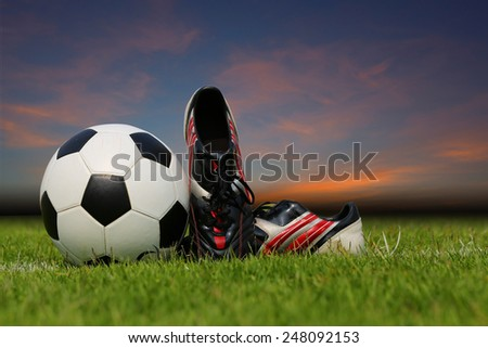 Display of football ball and soccer shoe on the grass at dust time  - stock photo
