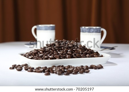 Display of roasted coffee beans with two cups - stock photo