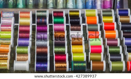 Display with spools of thread for fishing line of different colors to make fish hooks in fishing with fly  - stock photo