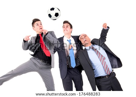 Displeased businessman paying a lost bet to a happy rival over a football game - stock photo