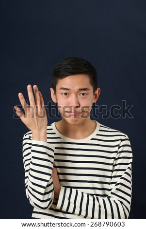 Displeased young Asian man gesturing with one hand and looking at camera - stock photo