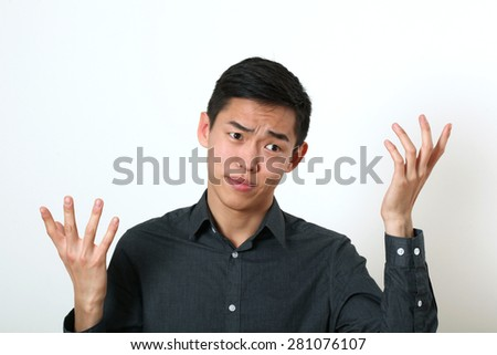 Displeased young Asian man gesturing with two hands. - stock photo