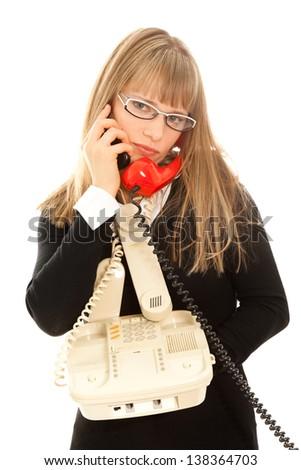Displeasured businesswoman with telephones - stock photo