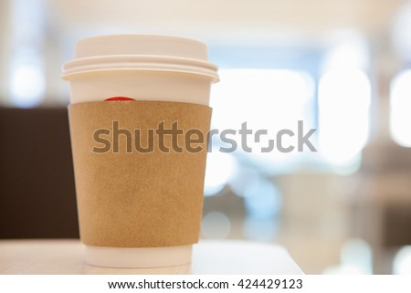 Disposable coffee cup on windowsill with city in background. - stock photo
