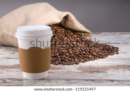 Disposable cup of coffee over vintage wood background with space for your text - stock photo
