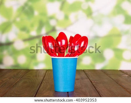 Disposable cups and plastic spoons on an abstract green background. - stock photo