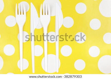 Disposable cutlery: white plastic forks and knifes on bright yellow polka dot background. Top view point. - stock photo