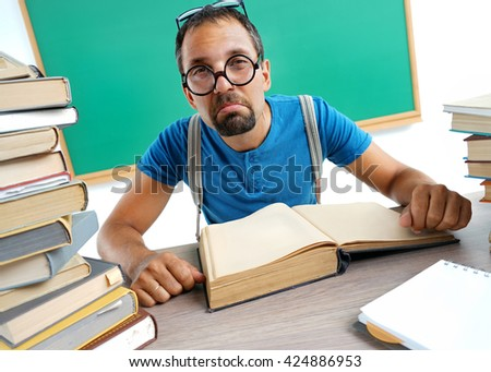 Dissatisfied teacher looking at camera. Photo adult man surrounded by books in classroom, education concept - stock photo