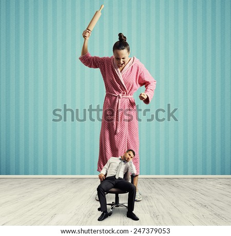 dissatisfied woman with rolling pin screaming at small lazy husband in room with blue wall - stock photo