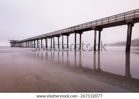 Distance landscape of a boat dock and low tide beach - stock photo