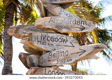 Distance to Moscow, Beijing, Amsterdam cities - wooden beach signs - stock photo