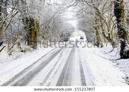 Distant car driving on winter snow covered country lane through woodland trees - stock photo
